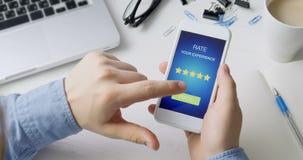 O homem dá uma avaliação de cinco estrelas usando a aplicação do smartphone vídeos de arquivo