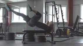 O homem da aptidão está encontrando-se no banco e levanta seus pés homem saudável que exercita Abdominals no gym vídeos de arquivo