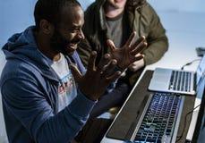 O homem da ascendência africana está trabalhando com portátil do computador foto de stock