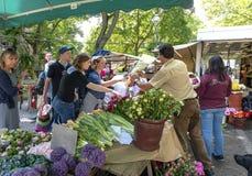 O homem 19-5-2018 da flor de Berlin Germany A em sua tenda no mercado vende suas flores a seus clientes, em um dia morno ensolara fotografia de stock royalty free