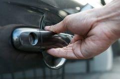 O homem da mão está abrindo um punho do carro imagem de stock
