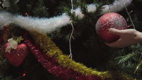 O homem da mão que decora na árvore de Natal com fulgor do Natal ilumina-se filme
