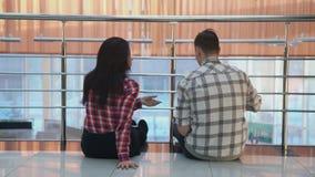 O homem da mulher que discute os assuntos, olhando documenta o assento no assoalho video estoque