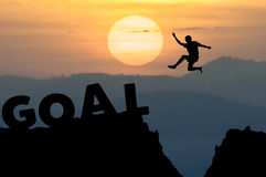 O homem da silhueta salta à palavra OBJETIVO com nascer do sol Fotos de Stock Royalty Free