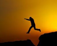 O homem da silhueta salta fotografia de stock royalty free