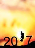 O homem da silhueta salta para fazer à palavra o ano novo feliz 2017 com nascer do sol Fotografia de Stock