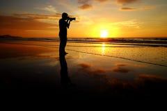 O homem da silhueta toma a imagem no fundo do por do sol Imagens de Stock Royalty Free