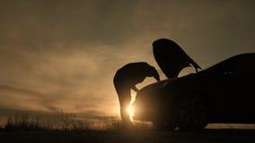 O homem da silhueta verificar a baía de motor do por do sol dividido do quando do carro video estoque