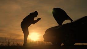 O homem da silhueta verificar a baía de motor do por do sol dividido do quando do carro filme