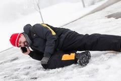 O homem da víctima está encontrando-se em uma maneira gelada e está chamando-se a ambulância Fotografia de Stock