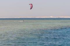 O homem das fotos da ação de Kitesurfing Kiteboarding entre ondas vai rapidamente Um surfista do papagaio monta as ondas fotos de stock royalty free