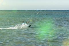 O homem das fotos da ação de Kitesurfing Kiteboarding entre ondas vai rapidamente Um surfista do papagaio monta as ondas iluminaç imagem de stock royalty free