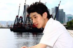 O homem de Ásia relaxa no parque na cidade Foto de Stock Royalty Free