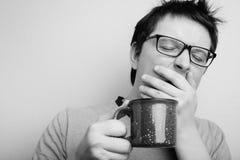 O homem de bocejo sonolento nos monóculos com o copo vermelho do chá ou do café tem cabelo uncombed no roupa interior no fundo cl fotografia de stock royalty free