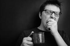 O homem de bocejo sonolento nos monóculos com o copo vermelho do chá ou do café tem cabelo uncombed no roupa interior no fundo pr fotografia de stock royalty free