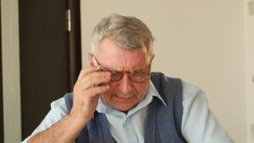 O homem de cabelo cinzento desembaraça palavras cruzadas, tem a visão pobre e está vestindo vidros filme