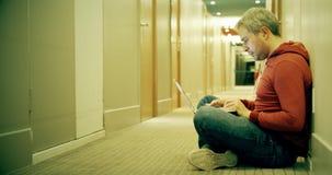 O homem de cabelo cinzento esperto na roupa ocasional usa seu portátil no corredor do hotel filme