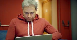 O homem de cabelo cinzento esperto novo na roupa ocasional usa seu portátil na entrada filme