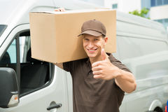 O homem de entrega com as caixas de cartão que mostram os polegares levanta o sinal Imagem de Stock Royalty Free