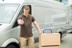 O homem de entrega com as caixas de cartão que mostram os polegares levanta o sinal Fotos de Stock