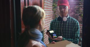 O homem de entrega feliz da pizza visita a casa com caixas a um cliente video estoque
