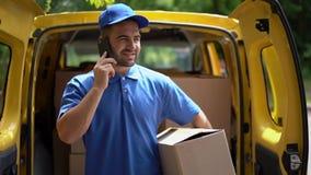 O homem de entrega no uniforme azul guarda uma caixa de cartão ao falar no telefone video estoque