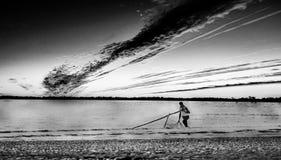 O homem de Fisher vê a praia fotografia de stock