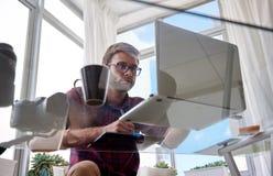 O homem de funcionamento novo disparou de debaixo de uma tabela de vidro Imagem de Stock Royalty Free