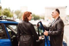 O homem de meia idade ajuda uma mulher a obter no carro fotos de stock royalty free