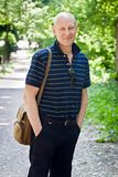 O homem de meia idade anda em um parque do verão fotos de stock royalty free