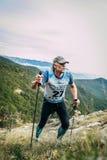 O homem de meia idade atrativo escala uma montanha com os polos de passeio do nordic fotos de stock royalty free