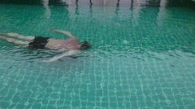 O homem de meia idade que relaxa e nada lentamente na piscina do hotel vídeos de arquivo