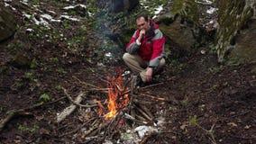 O homem de meia idade senta-se pelo fogo na floresta video estoque