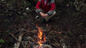 O homem de meia idade senta-se pelo fogo na floresta vídeos de arquivo
