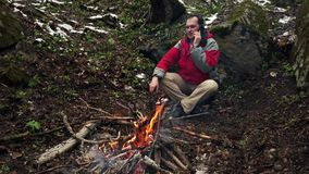 O homem de meia idade senta-se pelo fogo na floresta filme