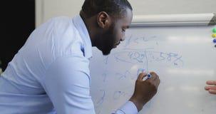 O homem de negócio afro-americano que escreve suas ideias na placa branca, empresários team discutindo o plano novo durante a reu filme