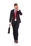 O homem de negócio anda com resumo & telefone imagem de stock royalty free