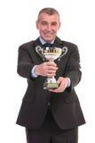O homem de negócio apresenta seu troféu imagem de stock royalty free