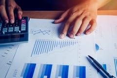 O homem de negócio asiático da mão do foco seletivo está calculando a finança e explicar fotografia de stock