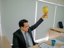 O homem de negócio asiático obtém o troféu dourado foto de stock royalty free