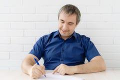 O homem de negócio assina um documento fotos de stock royalty free