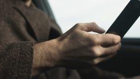 O homem de negócio bem sucedido fala pelo telefone que senta-se no close up do carro vídeos de arquivo