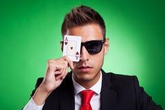 O homem de negócio cobre um olho com um ás de corações Foto de Stock