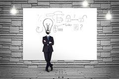 O homem de negócio com bulbo grande dirige pelo contrário Fotos de Stock Royalty Free