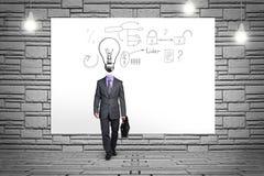 O homem de negócio com bulbo grande dirige pelo contrário Fotografia de Stock Royalty Free