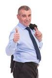 O homem de negócio com o revestimento sobre o ombro mostra o polegar acima Fotografia de Stock Royalty Free