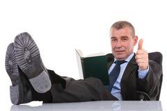 O homem de negócio com pés na mesa guarda um livro e mostra o polegar acima Fotos de Stock Royalty Free