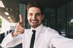 O homem de negócio considerável perto do centro de negócios que olha a câmera toma apontar do selfie imagens de stock royalty free