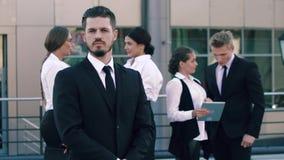O homem de negócio considerável que está no primeiro plano, no fundo seus trabalhadores companheiros está estando filme