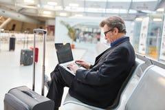 O homem de negócio está datilografando em seu portátil no aeroporto foto de stock